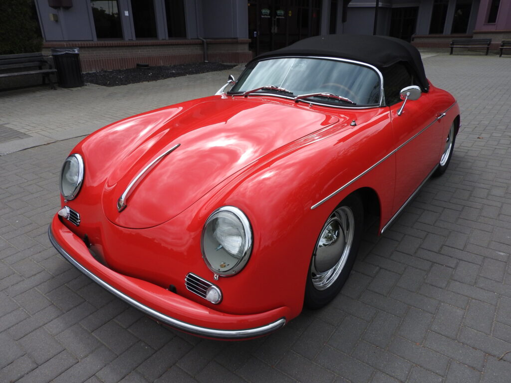 Red Intermeccanica Speedster with Black Convertible Top sits on cobbled plaza