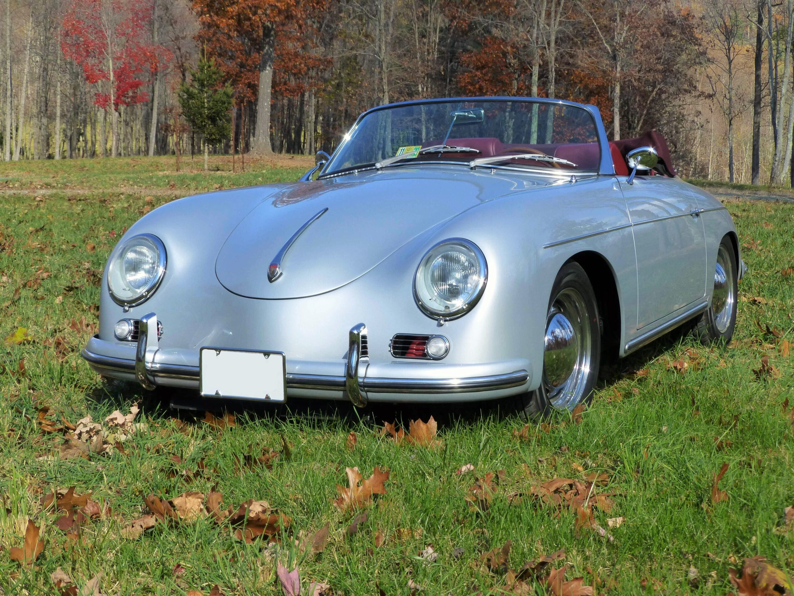 Silver 356 Roadster with red leather interior. Top is down and the vehicle sits in a grassy field